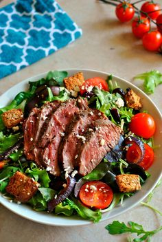 This Steak Salad with Caramelized Red Onions is full of amazing flavors! Feta, dried cranberries, cherry tomatoes, and homemade croutons all make this salad pop!