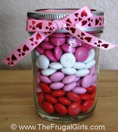 Valentine's M & M jar - Valentine's Day Bagged M's & divide by color. Layer in a jar, and tie with a pretty ribbon! Simple, thrifty and cute! {you can also cut a Valentine circle out of scrapbook paper to decorate the lid!} use with baby food bottles, too!