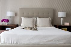 tufted headboard. matching nightstands. matching lamps. neutral monochrome.