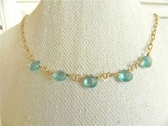 This is such a lovely, delicate necklace! The five tiny, faceted aqua , blue apatite briolettes are wrapped with gold filled wire to a chain that is 14 K gold filled. I have gotten more compliments on this necklace than any other that I have made. It is so simple, yet really brightens up your day.  Wearing this reminds me of a day at the beach under blue skies.  Great layering necklace!    *This is a delicate stone, so wash carefully in soapy water to remove oils occasionally and retain…
