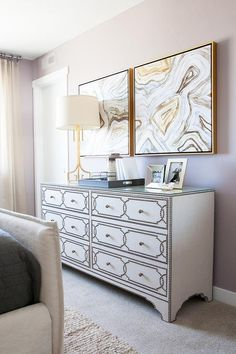 Beautiful bedroom features a 6 drawer nailhead dresser, Cabrillo Nailhead Dresser, topped with a gold Greek key lamp, Le Chic Gold Table Lamp, under gold and gray agate art pieces.