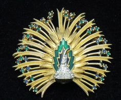 JOMAZ Vintage Rhinestone Enamel Goldtone  Peacock Brooch Attractive vintage designer signed JOMAZ figural peacock brooch. His feathers are fanned out and embellished with small emerald green rhinestones.