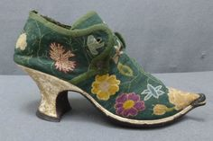 Cool for the day.....Woman's shoe, England, circa 1730. Finely embroidered with jonquils, roses, pinks, and other flowers in crimson, ivory, yellow, and pale blue on a mid green ground, the latchets with eyelet hole (for a ribbon), the slightly shaped tongue dipping in the centre, this and the edgings with applied linen braid, lined with brown cotton, the rand of ivory kid, leather straight sole.