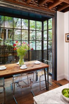 mooie combinatie van een groot raam, doorzichtige stoelen en een houten tafel