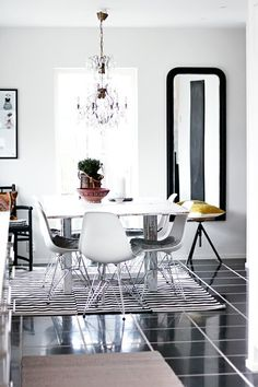 black and white dining room - a mix of mid-century with vintage-y chandelier and mirror and Ikea rand rug