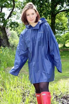 Cute girl in blue raincoat pantyhose and wellies
