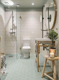 cuarto de baño: azulejos en blanco, muebles en madera natural y techo y suelos en color verde jade