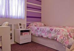 Por ser um ambiente pequeno, as arquitetas do escritório Rocha Andrade Arquitetura optaram por usar elementos suaves, como roupa de cama branca, que passa a impressão de amplitude. O toque feminino ficou por conta das cortinas e tapete lilás.