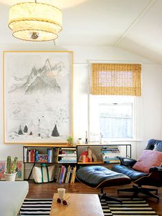 Monochromatic art and a simple color scheme keep this tiny San Francisco living room from feeling cramped. Books and accessories infuse the space with color.
