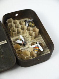 In which they store their honey ; Materials used: Tin, beads, wire, thread, an old map and book pages. All these materials are recycled. Dimensions (approx): 5cm wide, 8cm tall and 2cm deep. A wonderful gift for any bee lover, this little tin is filled with busy paper bees filling their comb with honey! It will stand perfectly on any shelf or an office desk and bring a smile to those who stop for a peek. The bees were made from small rolls of recycled paper and stand at around 2cm long. F...