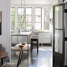 Gorgeous tall windows.  I like how the slender legs of the table and stools echo the thin vertical lines of each window = light and airy