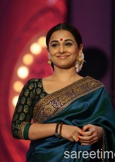 Blue and green double colour silk saree, with a gorgeous border; paired with a black and green blouse and flowers in her hair. And needless to say, we loved the red bindi. --- Vidya Balan in Sabyasachi