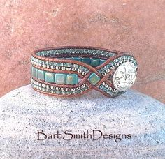 The Diamond Princess in Bronze Teal  The Diamond Princess is a slimmer version of my Queen of Diamonds. The focal point of this Princess is her two (2) diamonds of Bronze Picasso Teal Czech glass tile beads, woven into a distressed-finish light brown Indian leather cord. The center row is also done in tile beads, surrounded by (2) rows of seed beads in Nickel Oxide and Celsian Blue. The front closure is a double beaded loop surrounding a 3/4 silver flower button.  Measure your wrist! This…