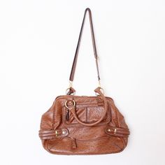 """Brown Ostrich Leather Satchel Purse Jessica Simpson 'Honor Roll' ⑊ MSRP $108.00  ⌁ Measurements: 11"""" height 17"""" length 6"""" depth 7"""" handle drop 17"""" strap drop  ⌁ Material: 100% PVC  ⌁ Condition: Used. Interior is a bit dirty. There are two tiny rips at the base of the back handles.  Comment below if you have other questions. Please make all offers using the """"offer"""" button. No trades or PayPal. No holds (first come, first serve). Comes from a smoke-free/pet-free home. Not responsible for…"""