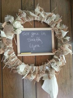 Burlap felt raffia and some felt flowers decorates the wreath. A chalkboard and a towel connected with a bamboo ring makes it functional.