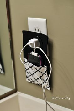 """iPhone holder: original blogger states: """" I used black fabric for the back, stregthened with heat and bond and quatrafoil fabric for the pocket.  I sewed all the way around everything.  Then I took a large grommet (for curtains) and put it through the top where it hangs onto the charger.  After I took this picture I added some black ric rac to the top of the pocket to finish the edge."""""""