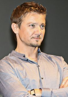 Jeremy Wearing Open-Necked Button-Up Light Brown Shirt With Arms Crossed in Front of His Chest