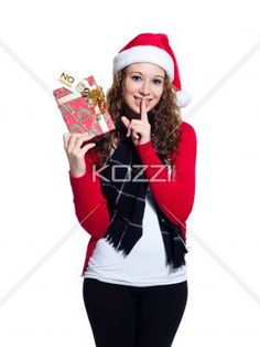 portrait of a woman holding a christmas present with finger on her lips. - Portrait of a woman holding a Christmas present with finger on her lips over white background, Model: Brittany Beaudoin