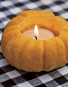 Pumpkin Votive  For an autumn table, carve out jack-be-little pumpkins and insert votive candles. This festive decoration can be used for Halloween parties, as well as Thanksgiving feasts. TIP: Candles at the dinner table should never have a fragrance.  From Country Living