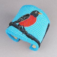 "Red Robin on Blue Item: HJ5069 Material: Beaded hide Size: Adjustable 5 3/4"" cuff, 2 7/8"" width Period: contemporary Origin: Kiowa Artist: Teri Greeves Price: $1,200.00"