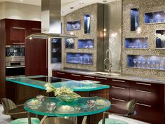 In place of upper cabinets, certified kitchen designer Elina Katsioula-Beall uses recessed, open cubbies inside a pebble-rock wall to showcase glassware, for a sleek, modern look.