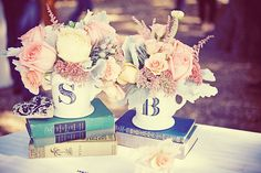 Lovely centerpieces using old books and flowers in monogrammed mugs
