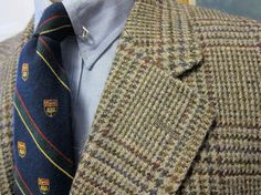 Beige plaid jacket, light blue shirt, navy tie with red, yellow, & green stripes