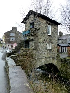 One up, one down - Ambleside, Cumbria, England. This is Bridge House which stands over Stock Beck in the middle of Ambleside. A 17th century survivor, it has had many practical uses over the decades, a counting house, a tea room, a weaving shop, a cobblers, a chair makers, and at one time a home for eight people! The mind boggles!
