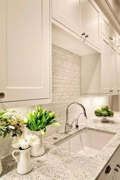 Kashmir white granite with a glass tile backsplash and chrome faucet. #kitchenrenovation #kitchentile
