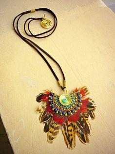 Collar largo de plumas y soporte hecho a mano en latón, inspiración nativa Amazónica. Decorado con mostacillas y piezas de latón. Parte trasera de cuero.