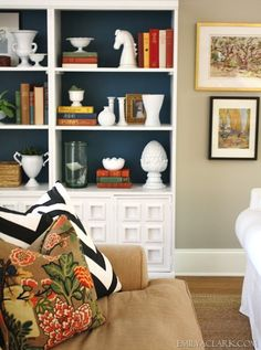 when styling a bookcase, try adding color to the back. You will be shocked at how it transforms your space if you have not already tried it. If you are afraid to permanently color your bookcases you can use fabric, wrapping paper, or painted cardboard. There are really so many options when it comes to adding color or pattern to the back of  your shelves.