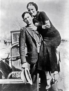 Bonnie Parker and Clyde Barrow posing with an early 1930s Ford V-8 automobile, 1932-1934.
