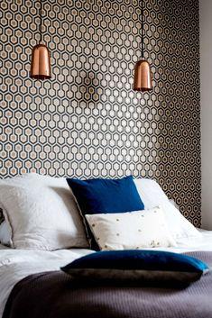 En guise de tête de lit, un papier peint graphique aux détails cuivrés