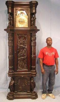 Monumental carved oak 5-tube grandfather clock with elite movement, 9 feet tall by 3 feet wide.    Also offered: a two-piece Allen & Brothers Victorian rosewood bedroom suite with gold incising; a long mahogany Federal dining table with claw feet and accordion fold (dated 1819, Philadelphia, Pa.); and a Federal mahogany settee, with carved arms and feather carved feet.