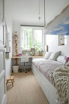 long narrow bedroom with desk under the window and storage under the bed