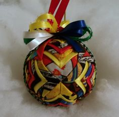 "Indian Handmade Quilted Ornament:    This 3"" handmade quilted ornament is made with a Indian Pottery fabric with bright colors. I layered yellow and red satin ribbon to add that pop to the ornament. This ornament is done in a new pattern called the cathedral. The top of the ornament is done in Red, green, white, yellow and blue satin ribbon. This ornament would look charming in your favorite bowl or basket or as a decoration in a room. It will make a great Christmas tree decoration! It makes ..."