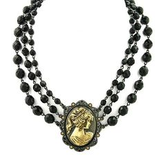 A gold tone vintage cameo pendant dangles from a triple strand beaded necklace chain. The three strands are graduated in size, letting it cascade on your collar beautifully.