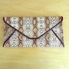 """Convertible snake color clutch Brown and white snake color clutch. Endless possibilities - wear it as a clutch, or wristlet, over the shoulder or cross-body. Comes with removable wrist holder and metal chain. 11""""x5.5"""", metal chain is 66"""" long. Magnetic closure. Brand new in packaging. Bags Clutches & Wristlets"""