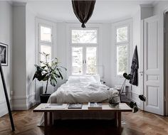 Dream on dreamer . Whats not to love about this stellar bedroom? It has all I could wish for: herringbone parquet wall panels plenty of light and the bed placed in front of the bay window plants and white bedsheets. @temporart totally rocked it! Listing: @husmanhagberg_stockholm Photo: @clearcutfactory #levaochbo