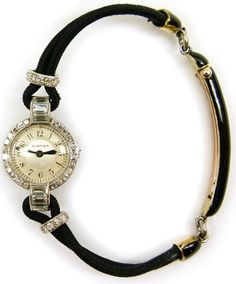 Late Art Deco diamond and platinum lady's wristwatch by Cartier, Paris c.1940, the round two-tone dial with black Arabic numerals, the bezel channel set with rectangular cut diamonds, curved lugs set with horizontal baguette diamonds, the platinum case with back-wind movement, numbered to verso 71624 and 4120? (rubbed), on a black cord strap with diamond set toggles, black enamel and gold deployant clasp, numbered 2480. Via S.J. Philips.