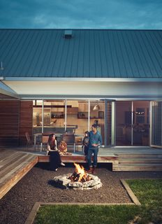 """Though the fire pit was """"kind of an after-thought,"""" says Hannah, the family uses it year-round. """"In the spring and fall, it warms you up on cool nights, and in the summer, it just adds ambience."""""""