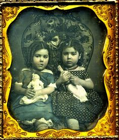 Antique photo of two little girls and their dolls, circa 1850 - 1870,