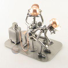 De tatoeëder prikt er nog een naaldje bij, dit voelt toch goed. Gewicht: 0.28 kg. Maten (h/b/d) in cm ca.: 13x16x10   Wilt u uw geschenk persoonlijk maken? Bestel er dan een grafeerbaar plaatje bij (artikel 10000). De metalen beeldjes, ook wel moerenmannetjes genoemd, zijn gemaakt in originele Steelman kwaliteit, uitvoerig en zorgvuldig handgemaakt. Als gevolg van deze afwerking is elk afzonderlijk metalenbeeldje uniek en voldoet aan de hoogste kwaliteitsnormen. Deze kleine stukjes van kunst…