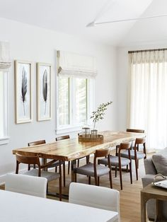 White and wood dining room with feather art