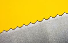 stainless steel knife against a yellow background