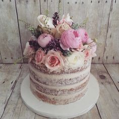 naked cake but with macaroons and carnations and 60 cake topper