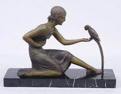 """D. H. CHIPARUS - Magnífica escultura francesa art deco, c. 1930, confeccionada em petit bronze com finíssimo trabalho à cinzel, fundição excepcional, representando """"dama com pássaro"""", apoiada sobre base em mármore preto portori, assinada na base D. H. Chiparus. Peça para colecionadores. Med.: 37x50x13 cm. Obs.: base apresenta lascado em uma das pontas."""
