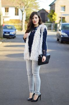 25 ways to wear a faux fur vest - dressy top, light wash skinny jeans + statement necklace