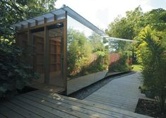 Multipurpose summerhouse in the UK functioning as an artist's studio, garden shed. The 8-meter mirror foil reflects the foliage and helps the structure disappear into the landscape. By Ullmayer Sylvester