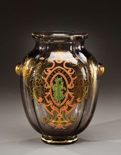 A black smoked glass vase with two heat applied cabochons and enamelled with a blazon and a dragon heightened in gold. Incised signature «E.Gallé à Nancy». Circa 1882-1885.